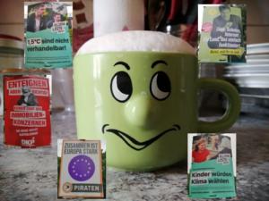 Auf dem Bild ist eine Tasse mit Gesicht zu sehen und fünf verschiedene Wahlplakate